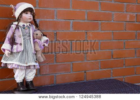 Background of a brick wall with doll stand. Big Doll