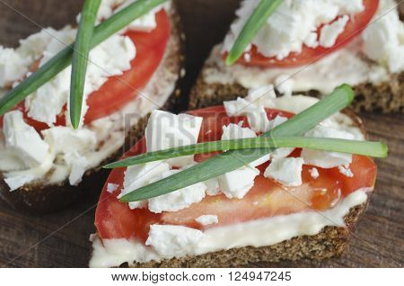slices of rye bread with sire feta, tomato and onion on a wooden board.  Selective focus.