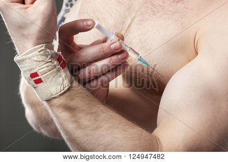 Close up of a muscular man injecting himself with steroids.
