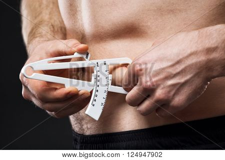 Young man is measuring his body fat with calipers.
