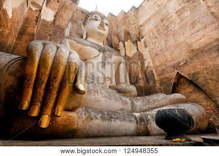 Big hands of praying Buddha inside small temple Wat Si Chum built in 13th century. Sukhothai historical park in Thailand is an UNESCO World Heritage Site.