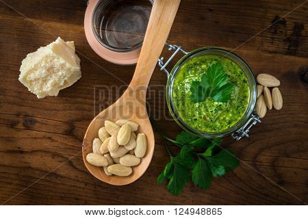 Pesto of parsley and almonds in a glass jar on a wooden table