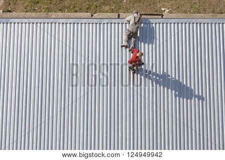 Szczecin, Poland - April 07, 2016: Workers Repairing A Store Roof Made Of Corrugated Metal Sheets, P