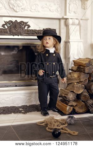 Girl as a chimney sweep against fireplace. Lucky New Year's Eve and New Year.