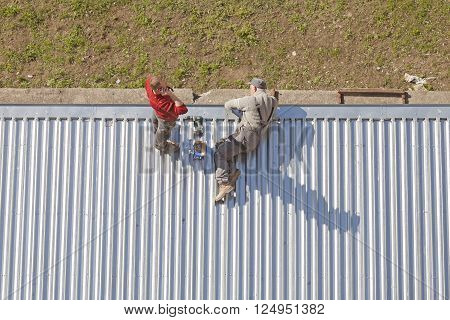 Szczecin, Poland - April 07, 2016: Two men working on a roof made of corrugated metal sheets, picture taken from above.