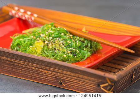 Fresh seaweed salad on a red plate in a bamboo server.