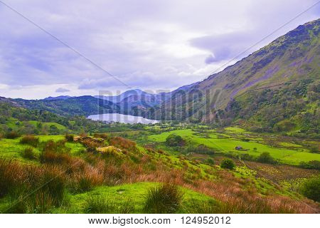 View to a mountain lake and a house in Snowdonia National Park in North Wales of the United Kingdom. Snowdonia is a mountain range and a region in North of Wales.