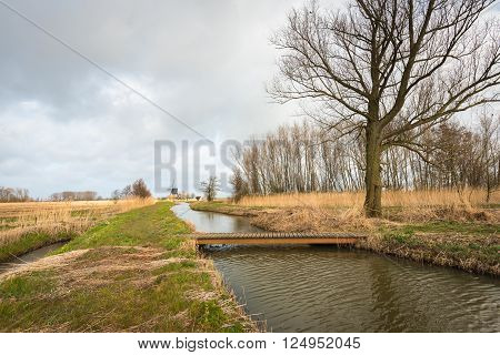 Simple wooden bridge made of planks bridges a small creek in a Dutch nature reserve on an overcast day at the beginning of spring. In the background an old windmill is visible.