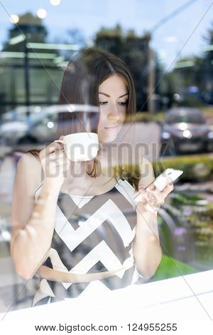Beautiful brunette girl with the glass showcase in a cafe reading a message on the phone, cup of tea, coffee, fashion, city, breakfast, writes sms business woman reflection in a window on the street