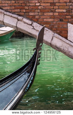 Close up of Gondola's Iron Prow and Antique Bridge in Venice Italy