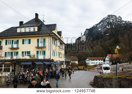 Schwangau Germany - January 06 2016: Walking tourists in Schwangau town against the Neuschwanstein Castle on a background winter time