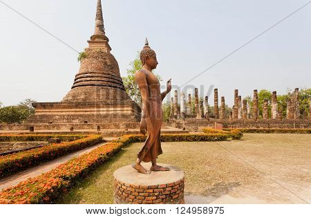 Walking Buddha statue past Buddhist stupa inside Sukhothai historical park Thailand. UNESCO World Heritage Site.