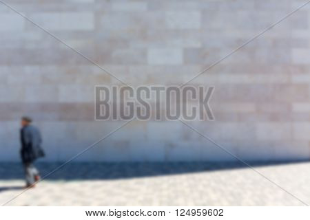 Man in front of stone wall on sidewalk blurred as Background