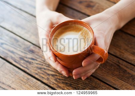 A cup of Cappuccino in female hands on a background of a wooden table. The concept of relaxing in the cafe relaxing time in a cafe dreams of love etc. ** Note: Visible grain at 100%, best at smaller sizes