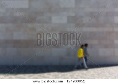 Two men in front of stone wall on sidewalk defocused
