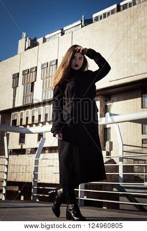 Pretty teenage girl in black coat walking on a city street
