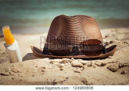 A hat with sunglasses and a bottle of sunscreen lotion lying on the sand. Vacation theme. Toned effect