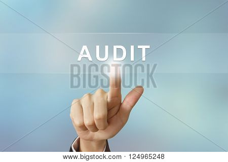 business hand pushing audit button on blurred background