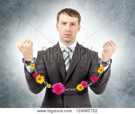 Businessman in cuffs with flowers on grey wall background