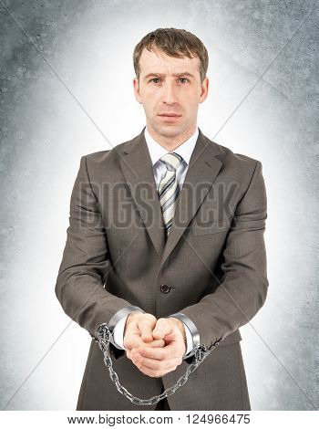 Serious businessman in cuffs on grey wall background