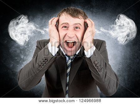 Screaming businessman looking at camera with smoke from his ears on grey wall background