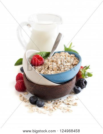 Rolled oats in a bowl with berries and milk isolated on white