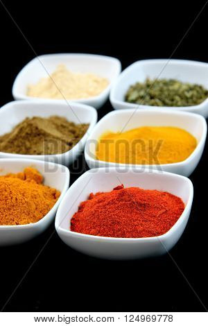 Colorful spice bowls on black background