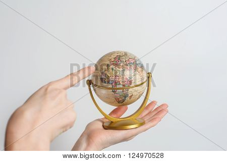 Female with small desktop globe of planet earth in hand. Forefinger pointing to Europe. White background.