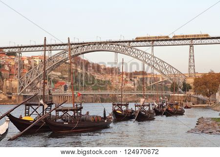 PORTO, PORTUGAL - November 24, 2014: traditional boats with wine barrels with the metro train on Dom Luis bridge and Porto city in the background