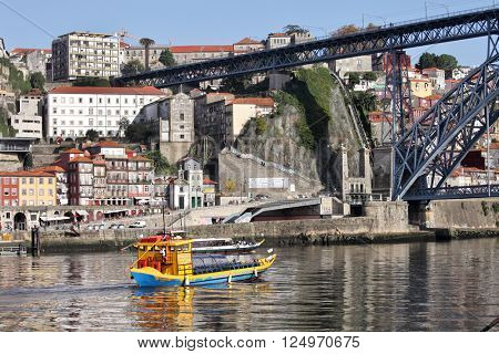 PORTO, PORTUGAL - November 24, 2014: View of the historic city of Porto with the Dom Luis bridge and tourist boat