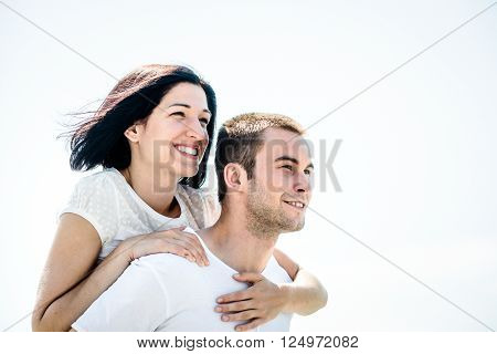 Young couple looking to bright future - happy woman embracing her love around neck