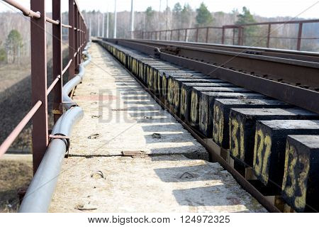 Cable and numbered sleepers on a railway bridge