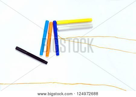 five markers of several colours on a white paper with orange lines