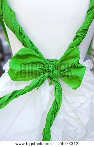green bow tied in a white doll