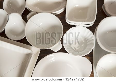 White porcelain dishes and utensils on a wooden background