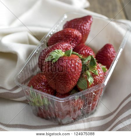 Strawberries in the plastic tray on napkin close up