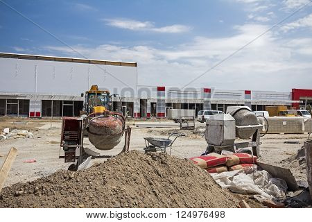 Cement mixer machine at construction site tools sand and cement bag.