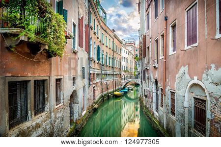 Beautiful narrow canal with silky water in Venice Italy