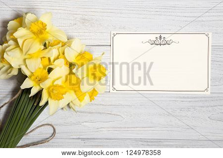 Daffodil bouquets and greeting cards on white wooden background