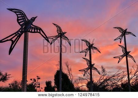 Metal birds flying into the sunset skies. Shoreline Park, Mountain View, California