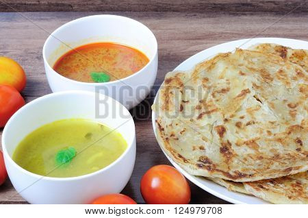 Roti canai or roti Prata with curry sauce and Dhal curry sauce famous Malaysian food.