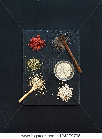 Superfoods on black chalkboard background: goji berries, chia, mung beans, buckwheat, quinoa and sunflower seeds. Top view, copy space