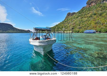 Fiberglass boat floating on a turquoise water in the Celebes sea.