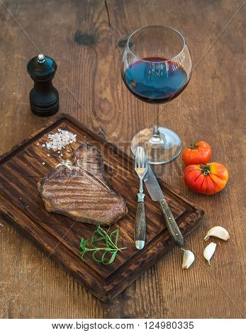 Cooked meat t-bone steak on serving board with garlic cloves, tomatoes, rosemary, spices and glass of red wine over rustic wooden background