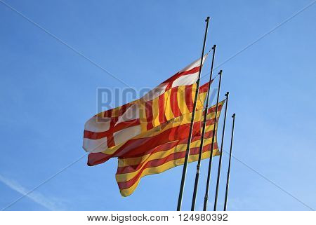 BARCELONA CATALONIA SPAIN - DECEMBER 13 2011: Catalan flag and flag of Barcelona fluttering in the wind