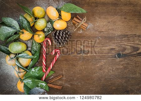 Christmas or New Year frame. Fresh mandarines with leaves, cinnamon sticks, pine cone and Christmas candy canes over rustic wooden background, top view, copy space