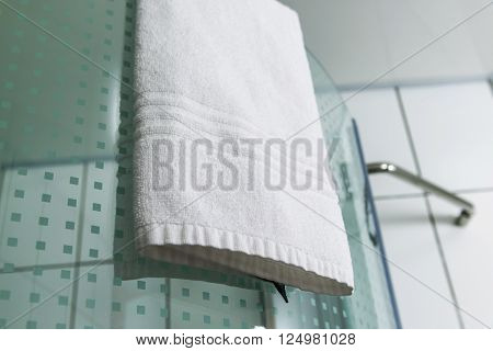 A white towels hanging on the shower ** Note: Shallow depth of field