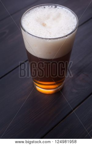 Shaker glass with ale on a dark wooden surface