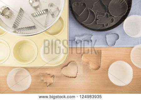 Metal pots and cake molds on a wooden background