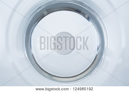 Round pill in glass of water. Top view. Concept of medicine.